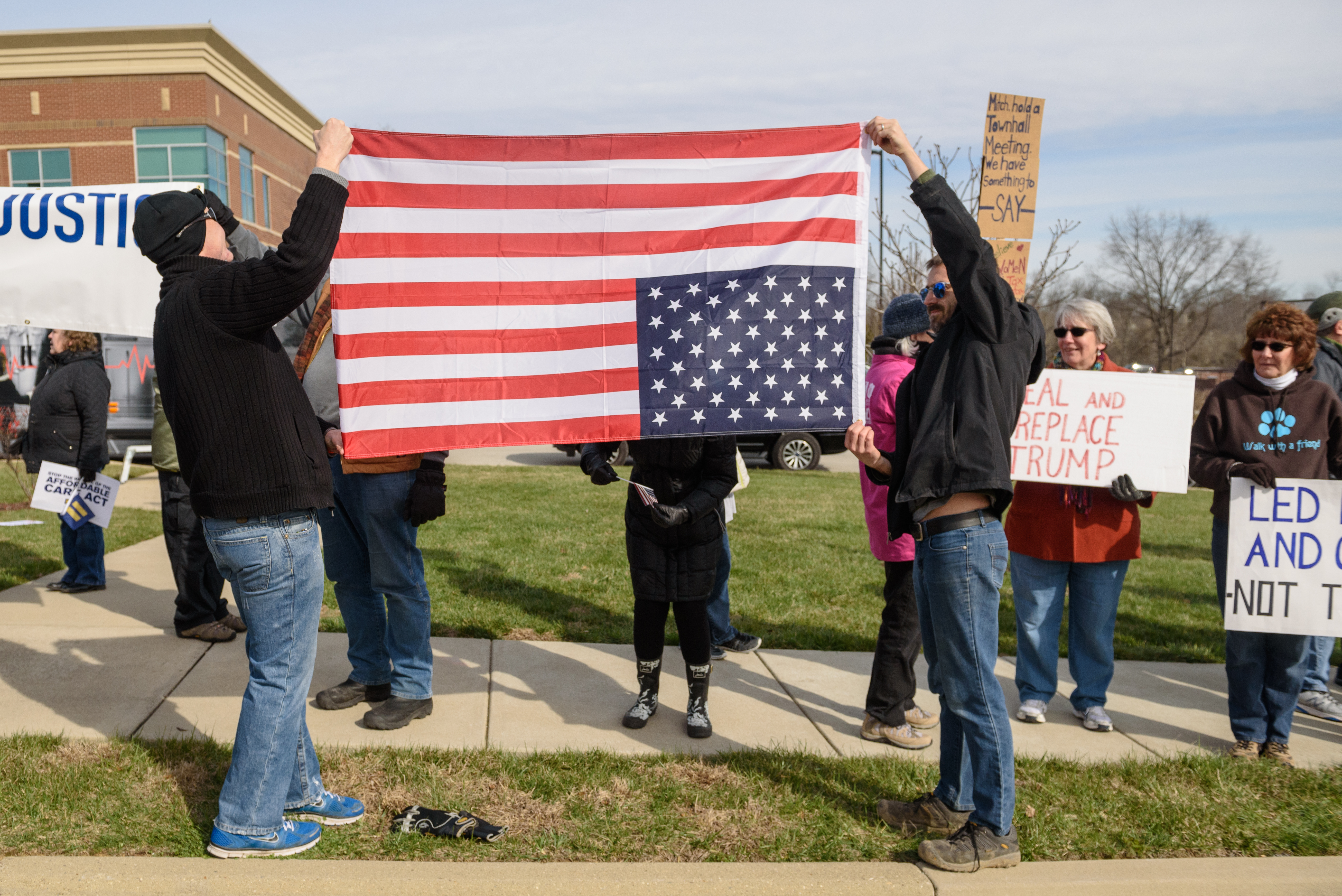 An American flag is held upside down, a sign of distress.