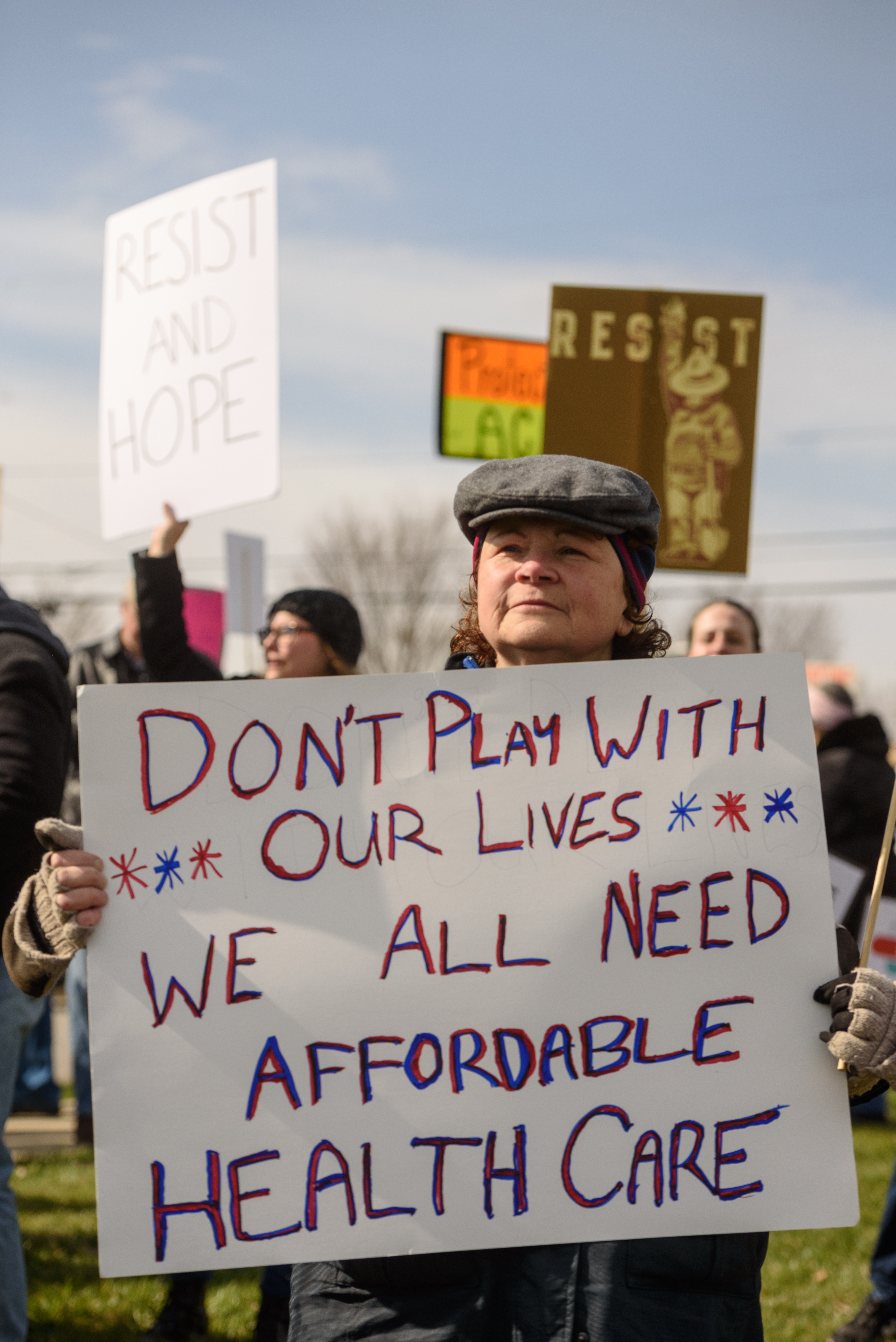 """Holding a sign that read, """"Don't play with our lives - We all need affordable healthcare,"""" Melinda Feldman said, """"I'm here because I'm an American and I care about healthcare, and not just for myself."""""""
