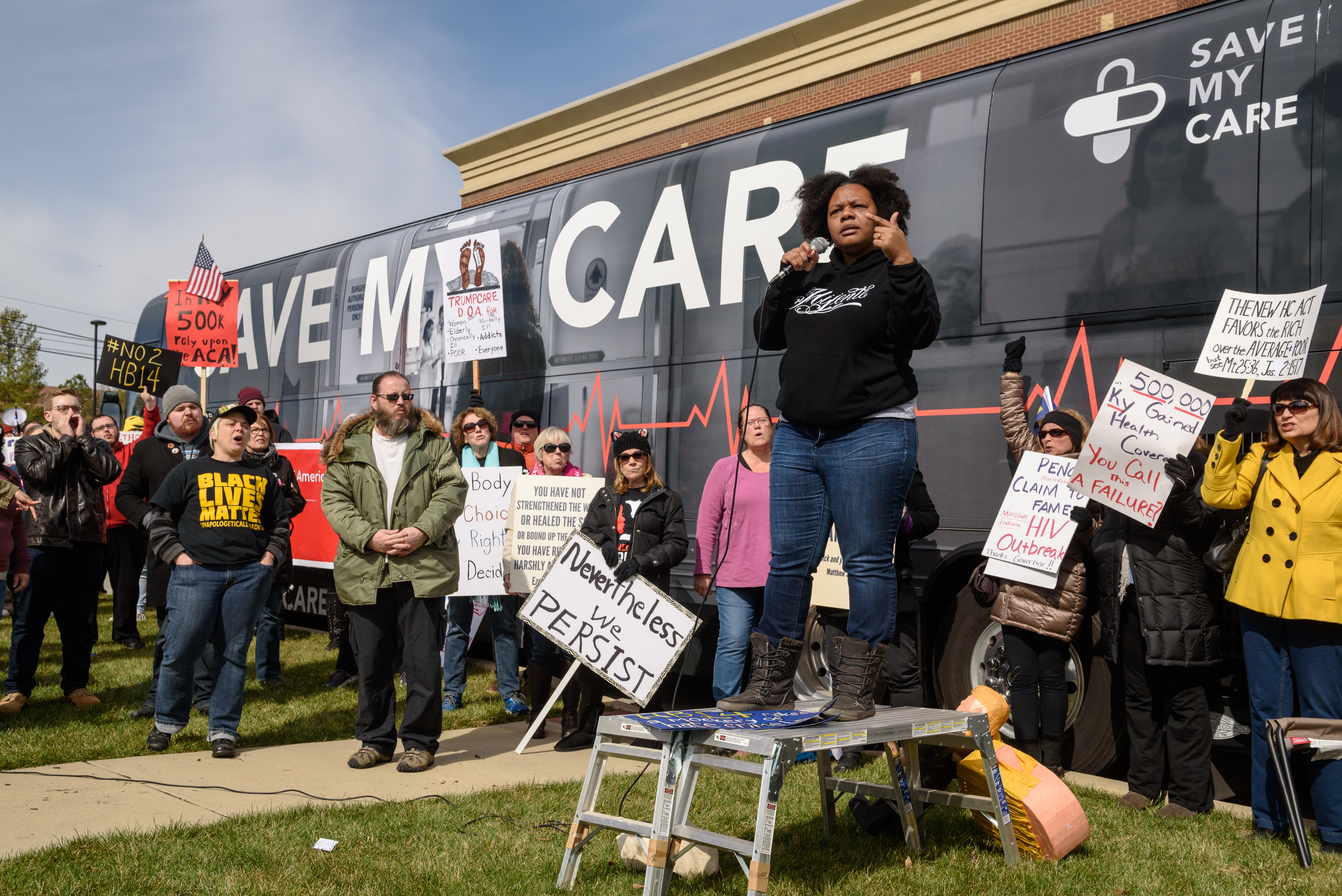 Chanelle Helm, a Black Lives Matter of Louisville organizer, delivers her message to protesters gathered in front of Indivisible Kentucky's Save My Care Bus.