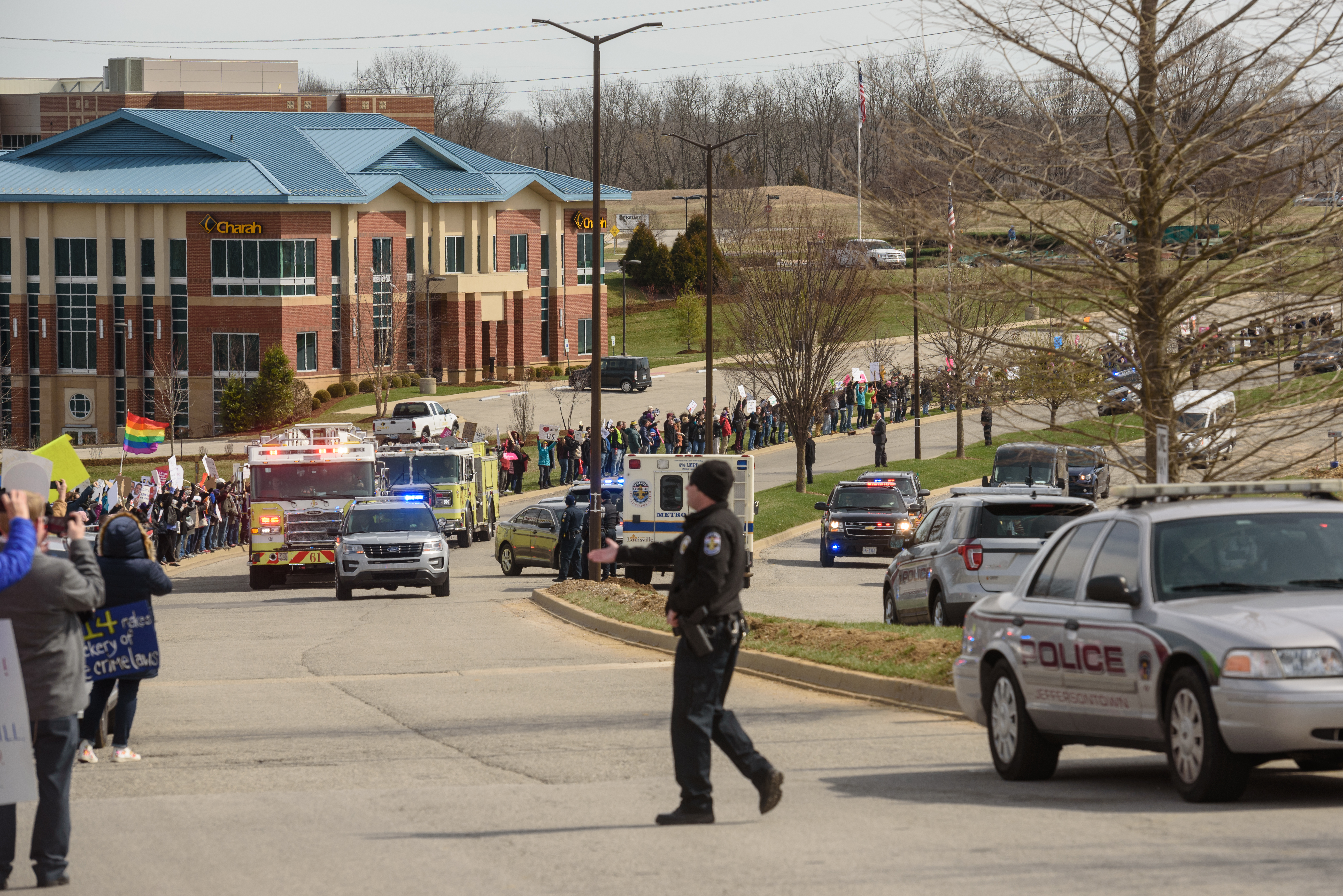 Two Jeffersontown Fire Department trucks, left, drive in front of protesters to block Vice President Pence's view as his entourage leaves the event Saturday.